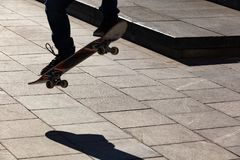 Sylwetka deskorolkarz który skacze na ulicie w mieście na deskorolka zdjęcie royalty free