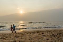 Sylwetka dwa przyjaciela widzieć jogging w seashore zdjęcia stock