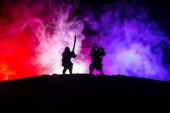 Sylwetka dwa samurais w pojedynku Obrazek z dwa zmierzchów niebami i samurais zdjęcia royalty free