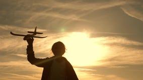 Sylwetka dzieci bawić się na samolocie Dzieci na tle s?o?ce z samolotem w r?ce dziewczyny sztuka z a zbiory