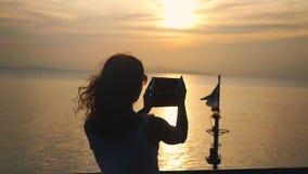 Sylwetka dziewczyna bierze fotografie zmierzch na telefon komórkowy kamerze podczas gdy podróżujący na statku wycieczkowym swobod zbiory