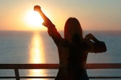 Sylwetka dziewczyna budzi się up rozciągający ręki w ranku wschodzie słońca zaświeca obraz stock