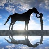 Sylwetka dziewczyna daje buziaka konia Zdjęcie Stock