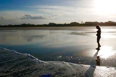 Sylwetka dziewczyna na plaży przy zmierzchem zdjęcie stock