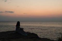 Sylwetka dziewczyna na zmierzchu tła wschodzie słońca na morzu fotografia stock
