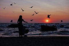 Sylwetka dziewczyna na zmierzchu tła wschodzie słońca na morzu zdjęcie royalty free