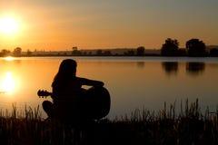 Sylwetka dziewczyna przy zmierzchem bawić się gitarę obrazy stock