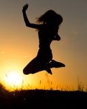Sylwetka dziewczyna skacze up przy zmierzchem Obrazy Stock