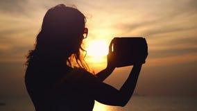 Sylwetka dziewczyna w okularach przeciwsłonecznych bierze fotografie zmierzch na telefon komórkowy kamerze swobodny ruch 1920x108 zdjęcie wideo