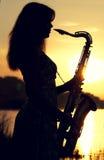 Sylwetka dziewczyna w sukni z mosiężnym instrumentem muzycznym w jego wręcza przyglądającego zamyślenie w odległość obrazy stock