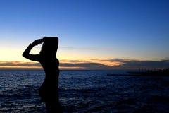 Sylwetka dziewczyny pozycja na wysokim morzu przy zmierzchem Fotografia Stock