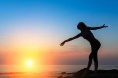 Sylwetka elastyczna dancingowa kobieta na dennym wybrzeżu podczas zmierzchu Fotografia Stock
