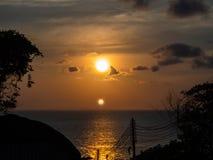 Sylwetka elektryczni druty przeciw słońca położeniu w morzu zdjęcia royalty free