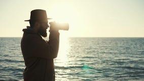 Sylwetka fotograf z kamerą na tle ocean powierzchnia zdjęcie wideo