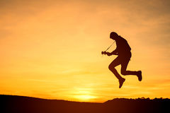 Sylwetka gitara gracz skacze na kamieniu Zdjęcie Royalty Free