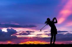 Sylwetka golfista bawić się golfa przy pięknym zmierzchem Zdjęcie Stock