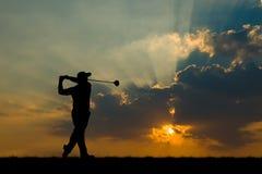 Sylwetka golfista bawić się golfa przy pięknym zmierzchem Fotografia Stock
