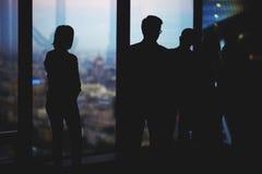 Sylwetka grupowi młodzi zdecydowani finansiści prowadzi rozmowę podczas gdy stojący w nowożytnym biurowym wnętrzu zdjęcia stock