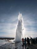 Sylwetka, grupy turystycznego dopatrywania gorącej wiosny naturalny gejzer wybucha w Strokkur, Iceland Obrazy Stock
