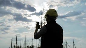 Sylwetka inżynier elektryczności opowiadać i use telefon podczas zmierzchu zbiory wideo