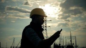 Sylwetka inżynier elektryczności opowiadać i use telefon podczas zmierzchu zbiory