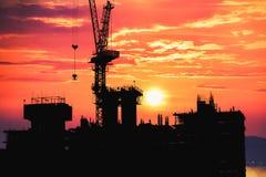 Sylwetka inżyniera kontroli praca i pracownik pozycja na wyższości budowy budynku przy wieczór przyśpieszać z czasem zdjęcie stock