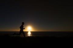 Sylwetka jogger wzdłuż oceanu horyzontu przy zmierzchem Fotografia Royalty Free