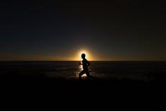 Sylwetka jogger wzdłuż oceanu horyzontu przy zmierzchem Zdjęcie Royalty Free