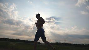 Sylwetka jogging w wiejskiej drodze przy zmierzchem mięśniowy mężczyzna Męski jogger szkolenie dla maratonu biega plenerowego atl Zdjęcia Royalty Free