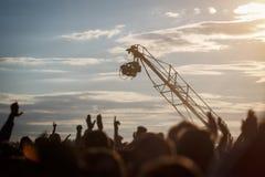 Sylwetka kamery telewizyjnej obwieszenie na żurawiu pracuje na plenerowym festiwalu muzyki Obrazy Royalty Free