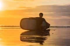 Sylwetka kipiel mężczyzna obsiadanie z surfboard na seashore zdjęcia royalty free