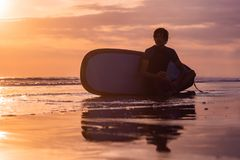 Sylwetka kipiel mężczyzna obsiadanie z surfboard na seashore obraz royalty free