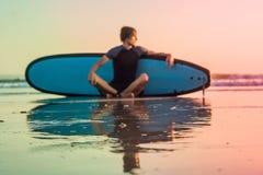 Sylwetka kipiel mężczyzna obsiadanie z surfboard na seashore plaży przy zmierzchu czasem fotografia royalty free
