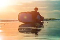 Sylwetka kipiel mężczyzna obsiadanie z surfboard na seashore plaży przy zmierzchu czasem zdjęcia royalty free