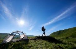 Sylwetka kobieta arywista blisko campingu przeciw niebieskiemu niebu w ranku fotografia royalty free
