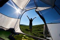 Sylwetka kobieta arywista blisko campingu przeciw niebieskiemu niebu w ranku zdjęcia stock