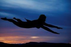 Sylwetka kobieta latający przylądek dalej fotografia stock