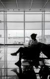 Sylwetka kobieta przy lotniskową poczekalnią Zdjęcia Royalty Free