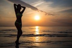 Sylwetka kobieta w bikini pozuje na plaży przy zmierzchem Obrazy Royalty Free