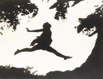 Sylwetka kobieta w powietrza doskakiwaniu między dwa drzewami Fotografia Stock