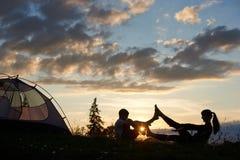 Sylwetka kobiety i chłopiec obsiadanie na trawie w joga pozie przy brzaskiem blisko namiotu Fotografia Stock