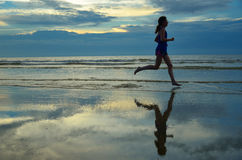 Sylwetka kobiety jogger bieg na zmierzch plaży z odbiciem Obrazy Royalty Free
