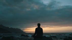 Sylwetka kobiety obsiadanie na ska?ach przy zmierzchem obserwuje ocean fale przy Benijo pla?? w Tenerife, wyspy kanaryjskie zbiory wideo