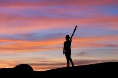 Sylwetka kobiety podnośny tripod pod niebem przy zmierzchem Zdjęcie Royalty Free