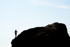 Sylwetka kobiety pozycja na skale Zdjęcie Stock