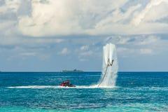 Sylwetka komarnicy deski jeździec przy morzem Fachowy jeździec sztuczki w błękitnej lagunie Tropikalny sporta wyposażenie Fotografia Stock
