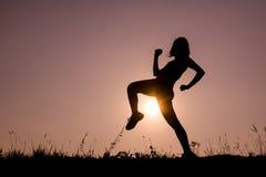 Sylwetka kopnięcie boksu dziewczyna ćwiczy kopnięcie Obrazy Royalty Free