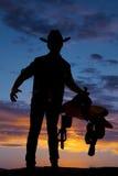 Sylwetka kowbojski mienie comber przy modną ręką out Zdjęcia Stock