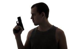 Sylwetka kryminalny mężczyzna mienia pistolet odizolowywający na bielu Obrazy Royalty Free