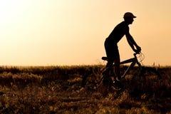 Sylwetka mężczyzna jedzie bicykl w polu Obraz Royalty Free